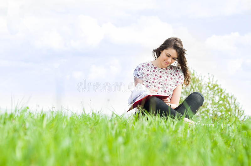 Young smiling woman sitting on meadow and writing something stock photography