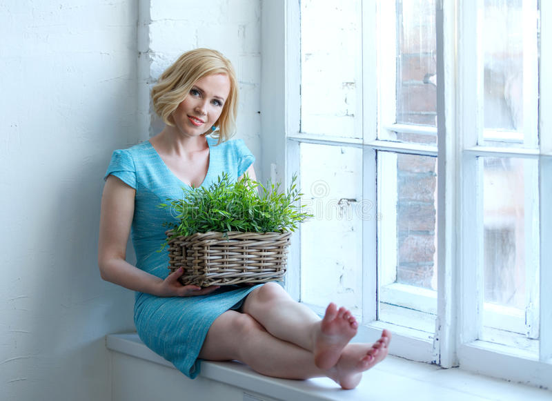 Young smiling woman sitting on windowsill with box with plants. royalty free stock image