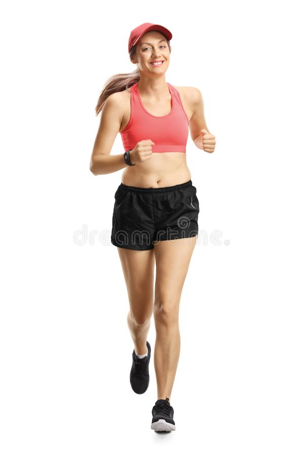 Young smiling woman in sportswear jogging towards camera stock image