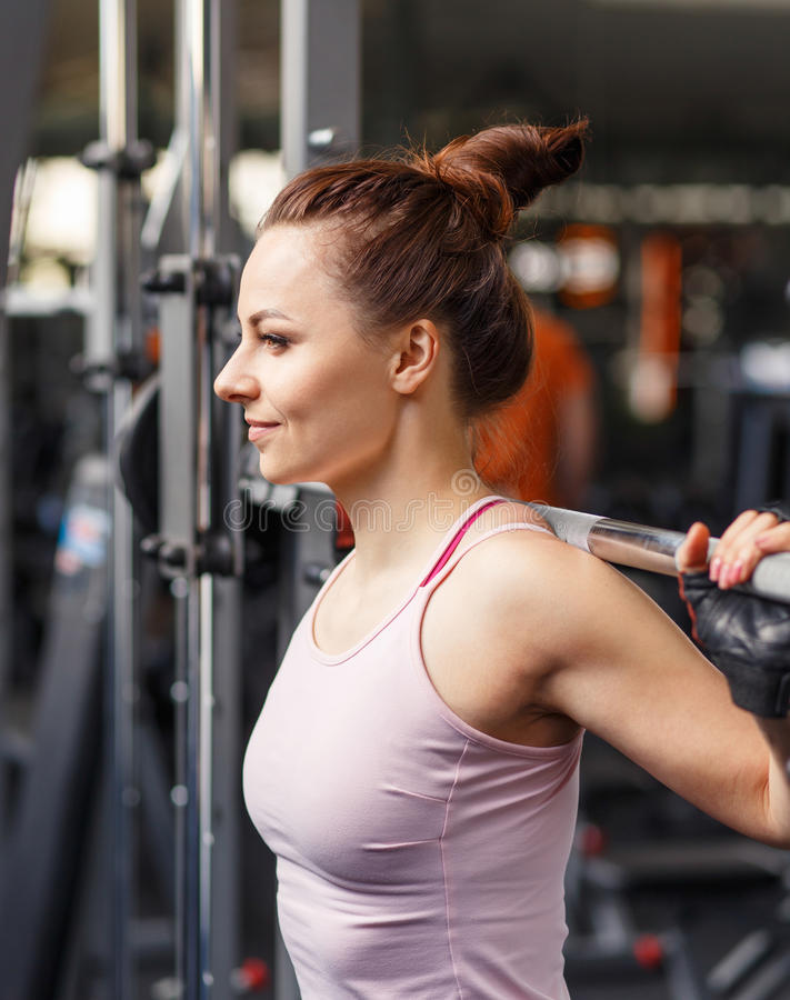 Young smiling woman squatting with barbell in gym royalty free stock image