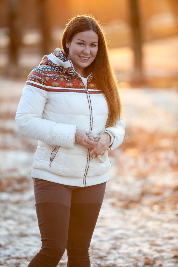 Young smiling woman stands in winter park in sunset light of sunset sun royalty free stock photo