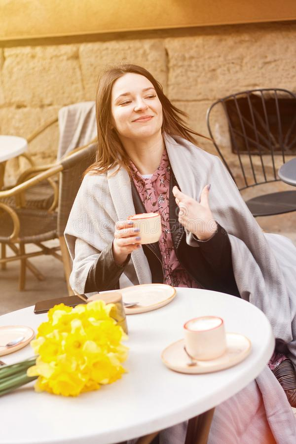 Cheerful young woman in a street cafe drinking coffee royalty free stock image