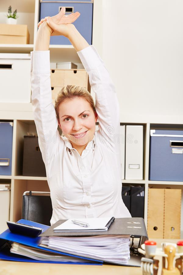 Young woman stretches arms in the office royalty free stock photos