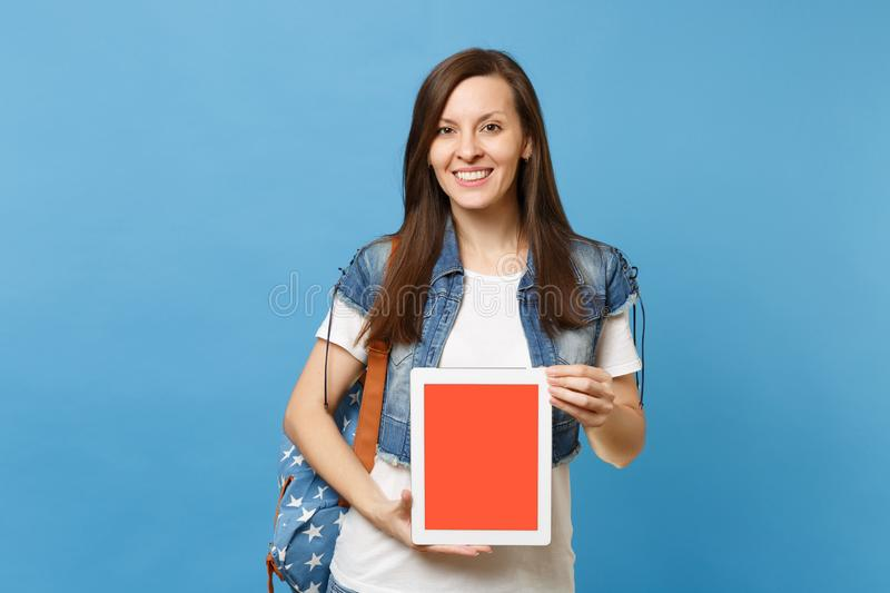 Young smiling woman student in denim clothes with backpack holding tablet pc computer with blank black empty screen stock images