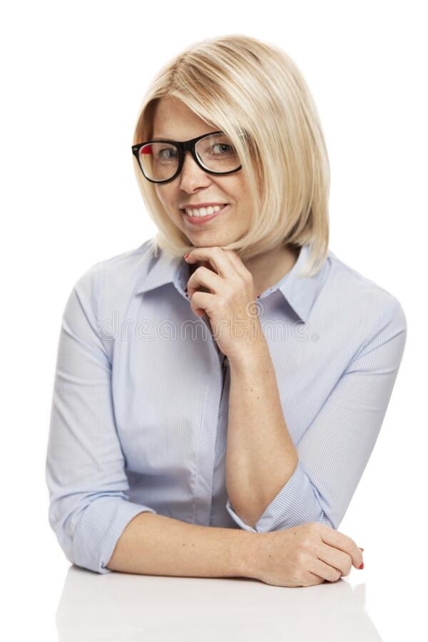 A young smiling woman in stylish glasses and a blue shirt is sitting at the table. Business success. Isolated on a white royalty free stock photo