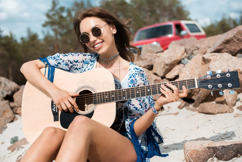 young smiling woman in sunglasses playing acoustic stock photos