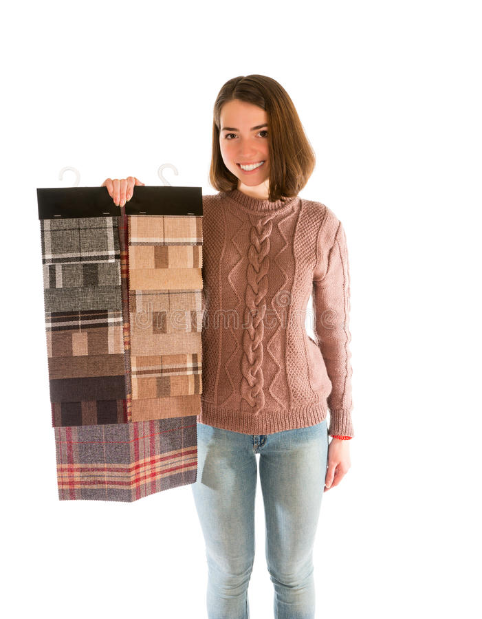 Young smiling woman in sweater holding fabric swatches. Isolated on white background royalty free stock photos