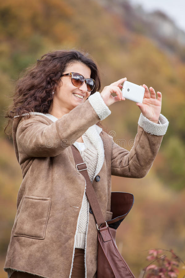 Young smiling woman take photo with mobile phone in autumn forest. royalty free stock images