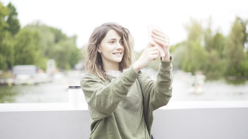 A young smiling girl is taking a selfie in the park stock image