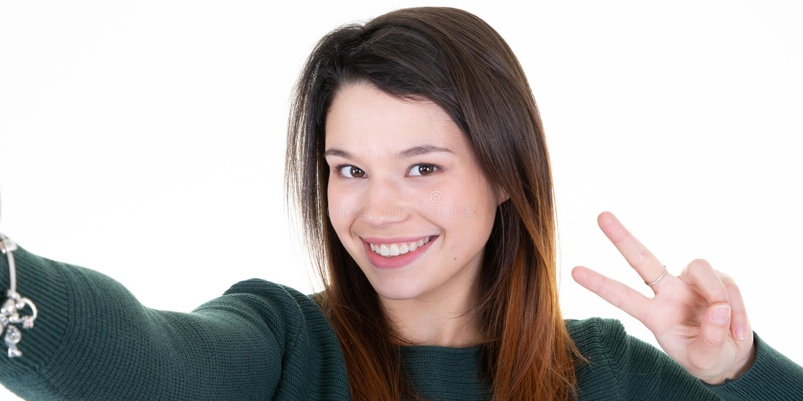 Young smiling woman taking a selfie  with phone making v victory sign hand fingers royalty free stock image