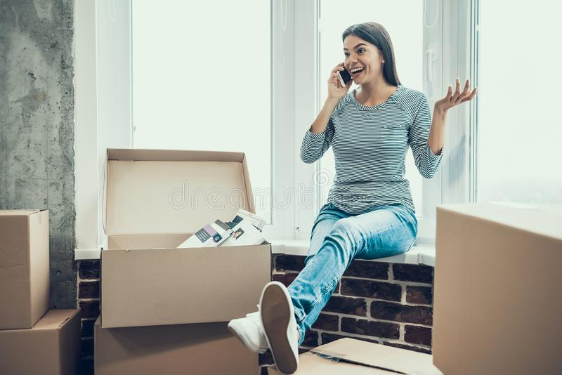 Young Smiling Woman Talking on Phone next to Boxes royalty free stock photography