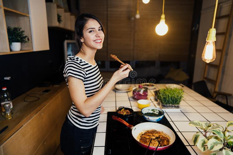 Young smiling woman tasting a healthy keto meal in home kitchen.Making dinner on kitchen island standing by induction hob. Preparing fresh meat and vegetables stock photography