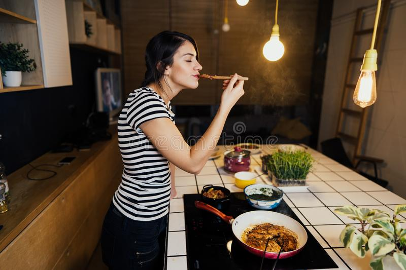 Young smiling woman tasting a healthy keto meal in home kitchen.Making dinner on kitchen island standing by induction hob. Preparing fresh meat and vegetables royalty free stock photo