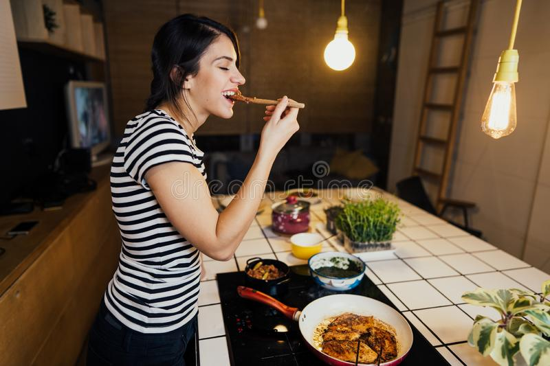 Young smiling woman tasting a healthy ketogenc meal in home kitchen.Making dinner on kitchen island standing by induction hob. Young smiling woman tasting a stock image