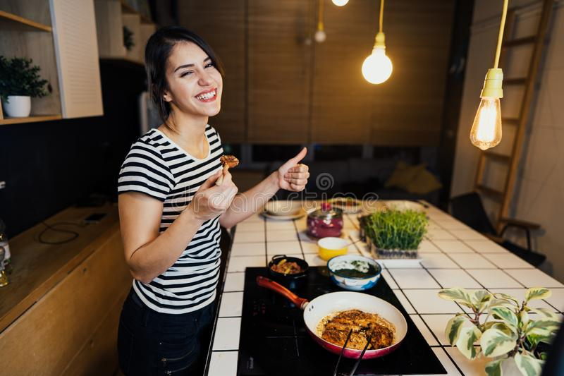 Young smiling woman tasting a healthy meal in home kitchen.Making dinner on kitchen island standing by induction hob.Preparing. Fresh vegetables,enjoying spice stock photography