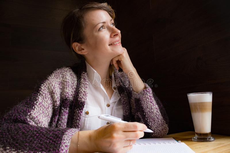 Young smiling woman thinking with pen and open notebook. Thoughtful girl portrait. Journalist and writer concept. Business lifesty stock photography