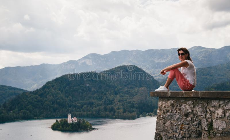 Young smiling woman tourist sitting on a Bled Castle wall with the lake Bled and the Bled island on the background stock photos