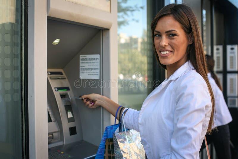Young smiling woman using card at ATM . Looking at camera. royalty free stock photos
