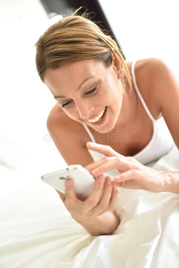 Young smiling woman using smartphone royalty free stock photos