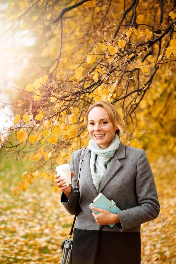 Young smiling woman walking and drinking take away coffee stock image