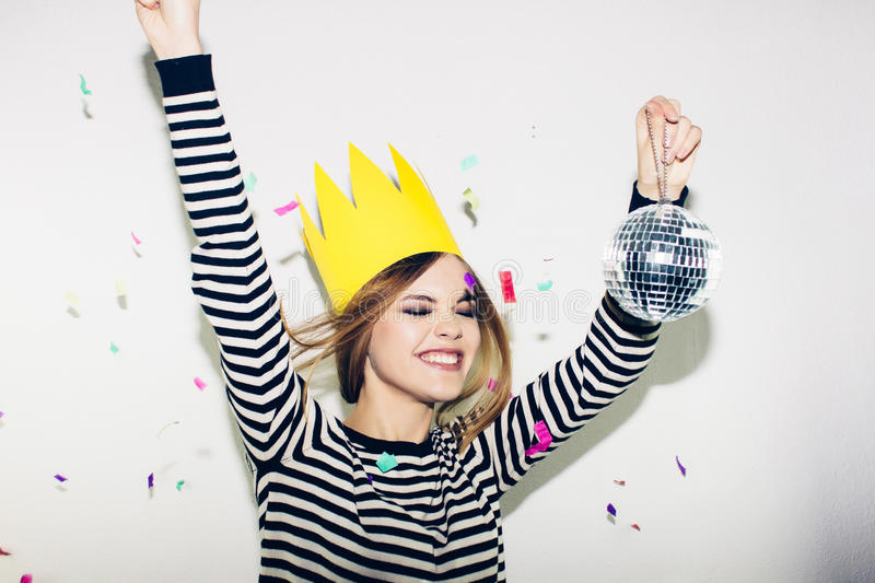 Young smiling woman on white background celebrating party, wearing stripped dress and yellow paper crown, happy dynamic stock photo