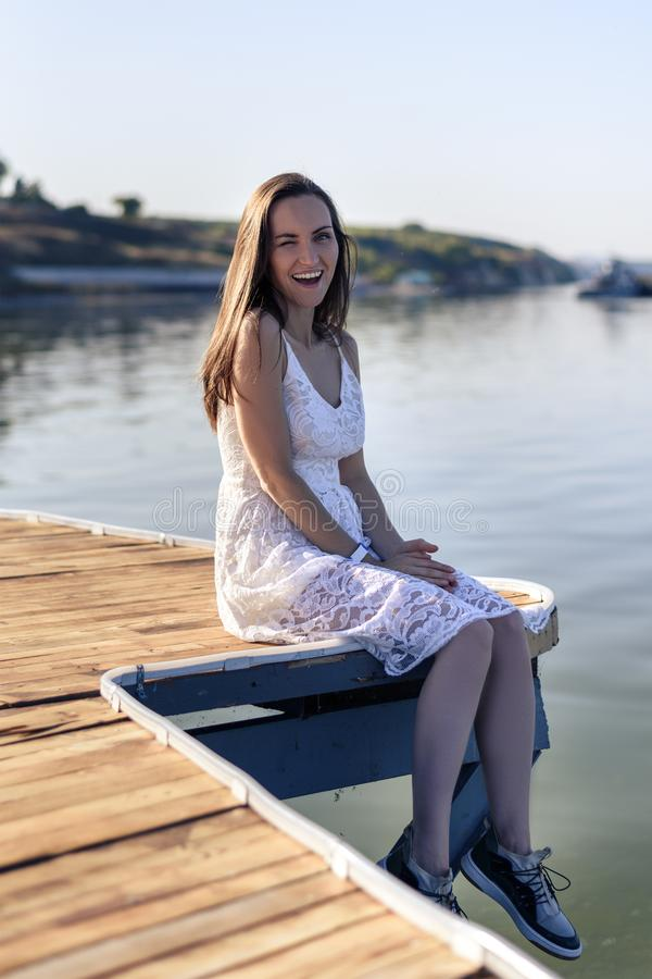 Young smiling woman winks her eye, sitting on the pier in a white sundress stock photo
