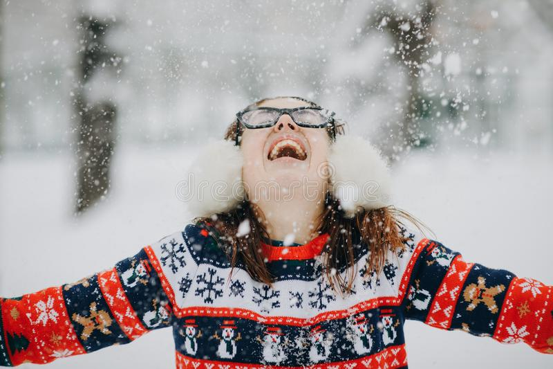 Young smiling woman in winter jacket throwing snowflakes. Happy female in beautiful pine forest on mountain top royalty free stock photography