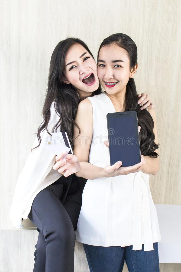 Young smiling woman 20-30 years.Portrait of couple h. Young smiling women 20-30 years.Portrait of couple holding tablet and credit card.Girls in white and black royalty free stock images