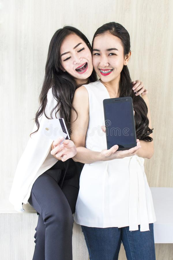 Young smiling woman 20-30 years.Portrait of couple h. Young smiling women 20-30 years.Portrait of couple holding tablet and credit card.Girls in white and black stock photography