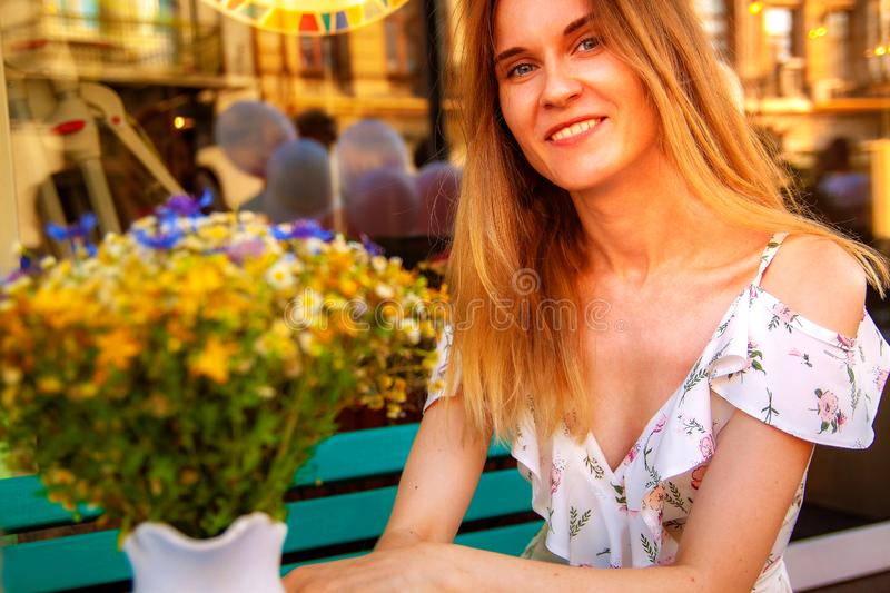 Young woman sitting at street cafe near flowers and green plants. Concept of cozy place in open air and resting. royalty free stock images