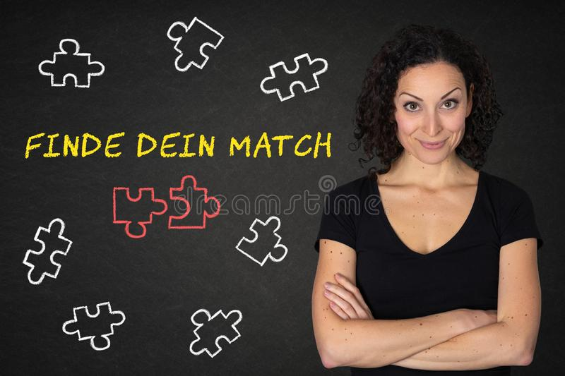Young smily woman with crossed arms,puzzle pieces and text `Finde dein Match` on a blackboard. Translation: `Find your match& x27; stock photography