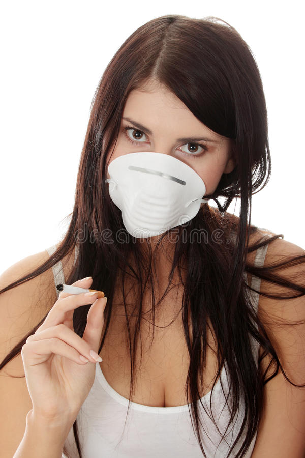 Young smoking woman with face mask. Isolated royalty free stock image