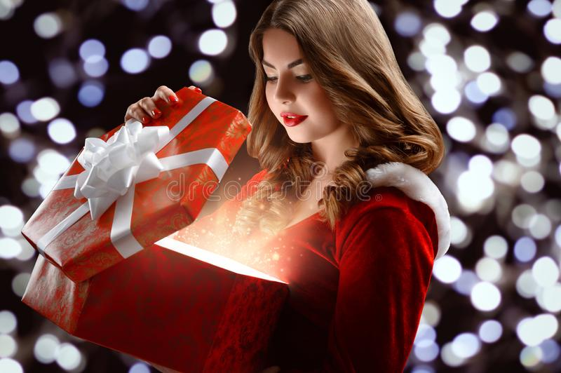Young Snow Maiden in the red suit opens a gift for New Year 2018,2019. Attractive girl in suit of Snow Maiden holds a gift for Christmas and New Year 2018,2019 stock images