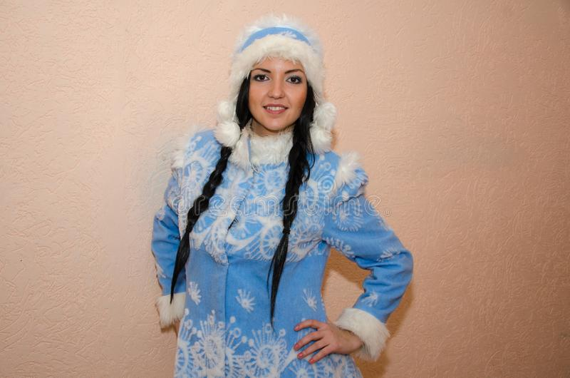Young Snow Maiden. Sexy woman dressed in the traditional Russian New Year`s costume Snow Maiden, a girl in a blue New Year`s sui royalty free stock image