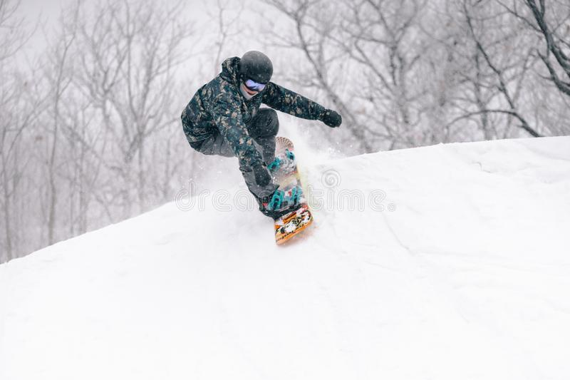 Young snowboarder drops into a half pipe royalty free stock images