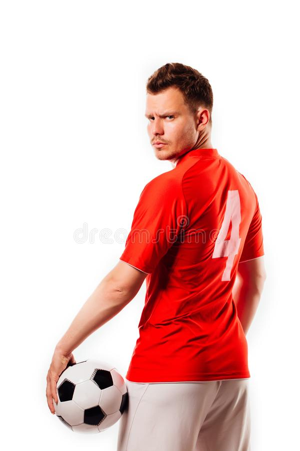 Young soccer player with ball on black background in studio. royalty free stock images