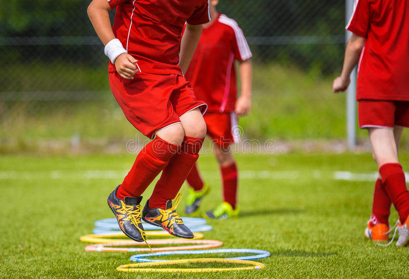 Young Soccer Player Practicing on the Pitch. Soccer Football Equpment. Dynamic Jumping Football Practice stock photography