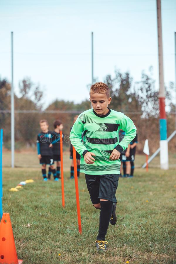 Young soccer player running between cones and ring ladder marker stock image