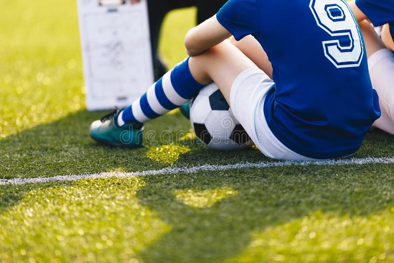 Young Soccer Player During Training Session. Children Sitting on Green Football Venue. Soccer Coaching Background. Sports Education royalty free stock photo