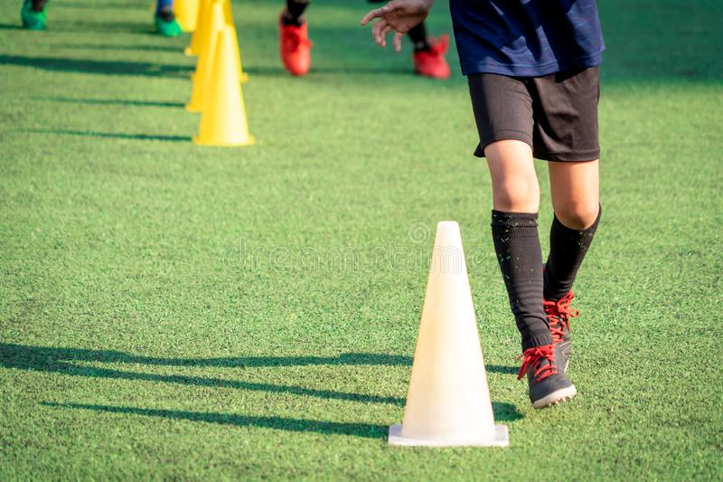 Young soccer player training with sport cone marker on green grass football pitch training ground royalty free stock images
