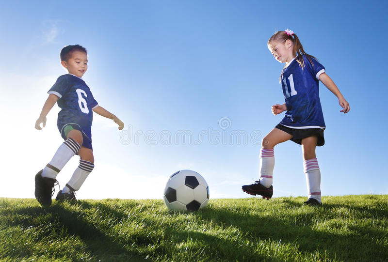 Young Soccer Players Kicking Ball. Two Young soccer players kicking a ball royalty free stock photos