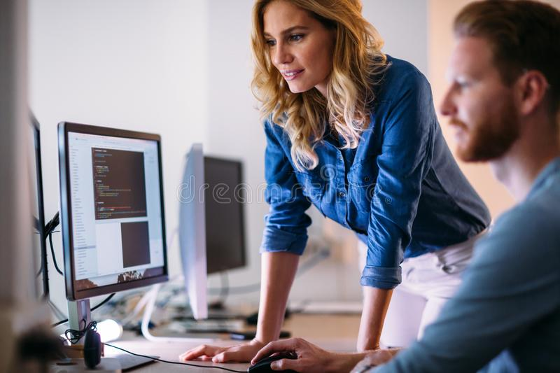 Software engineers working on project and programming in company stock images