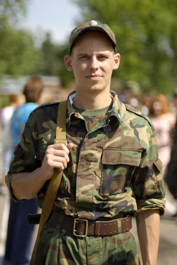 Young soldier. Poses with some civilians in the blurred out-of-focus background royalty free stock photo