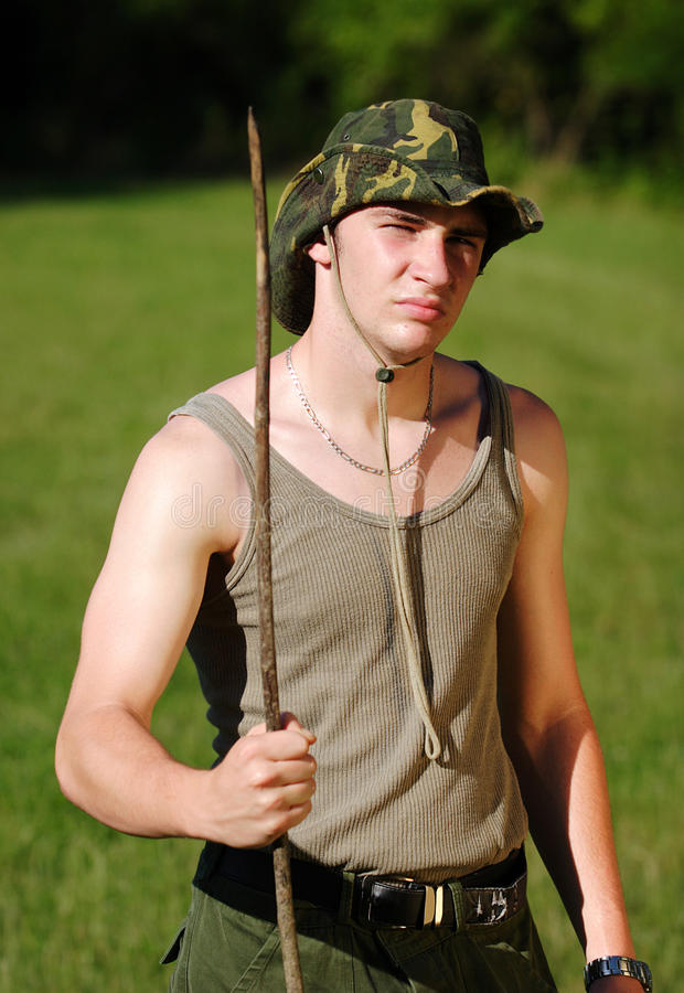 Young soldier. In khaki cloth stay with wooden lance stock image