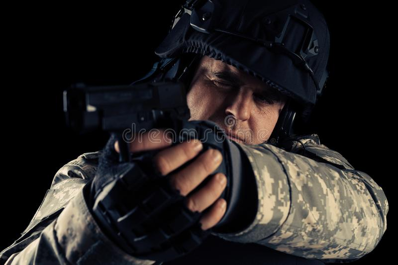 Soldier aiming with black pistol. Image on a dark background. Young Soldier aiming with black pistol. Image on a dark background royalty free stock photos