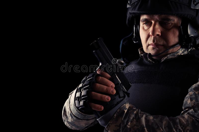 Soldier aiming with black pistol. Image on a dark background. Young Soldier aiming with black pistol. Image on a dark background stock photos
