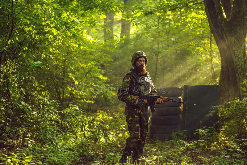 Soldier with rifle in forest. Young soldier bearded man in military camouflage and helmet with rifle in hands standing on post on background of green trees of stock photos