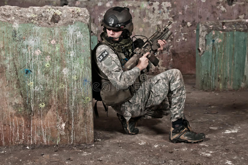 Young soldier behind obstacle. Young soldier in ruined building behind obstacle, aiming. air soft gun player stock image