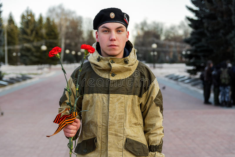 Young soldier in camouflage. Yoshkar-Ola, Russia. December 17, 2015: A young cadet in camouflage with flowers before the ceremonial laying of flowers at the time stock images