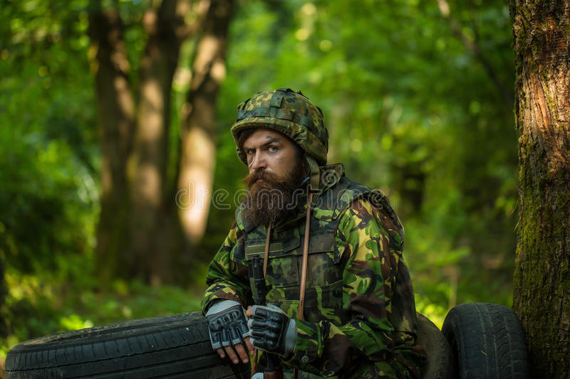 Young soldier on guard. Young soldier wirh bearded dusty tired face in military camouflage uniform with hanging camera and rifle in hand sitting on guard near royalty free stock photo